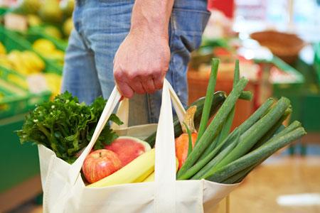 Personne qui tient un panier de légumes